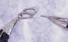 http://wirewoman.hubpages.com/hub/How-To-Make-A-Cone-Shaped-End-Cap-For-Wire-Jewelry