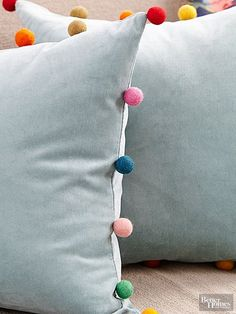 A few creative touches gave these basic pillows new life. To add pizzazz, the homeowner used felted-wool pom-poms found on Amazon to embellish the edges.