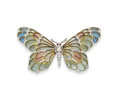 A DIAMOND AND ENAMEL BROOCH, BY CARTIER - Designed as an old mine and single-cut diamond butterfly with circular-cut ruby eyes, extending multi-colored plique-á-jour enamel wings, mounted in platinum and 18k gold