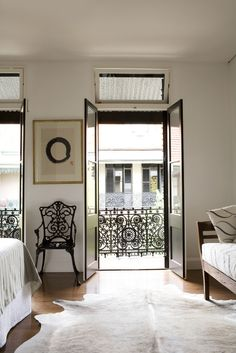 Paris? NO, Sidney!! The cast iron chair in the bedroom echoes the detailing on the balcony. This Victorian terraced house in the middle of Surry Hills, Sydney, is opened up to take advantage of a lush garden.  Australian architect Hannah Tribe of Tribe Studio Architects redesigned this house for a catering couple in the Surry Hills neighborhood.