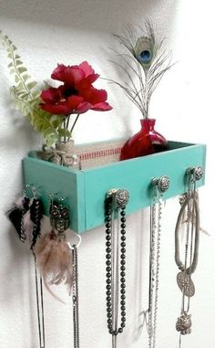 Drawer upcycled to a jewelry rack. I like the use of knobs and the hooks for earrings as well as the option to just toss stuff in the box when you are in a hurry.