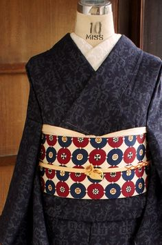 こっくりと深い黒に近い濃紺の地に、ネイティブデザインを思わせるようなフォークロアテイストただよう幾何学模様が織り出された正絹紬の袷着物です。