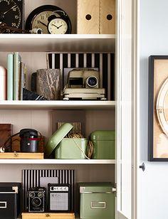 Nahaufnahme eines hohen IKEA Aufbewahrungselements mit geöffneten Türen. Darin sind Kameras und SNIKA Kästen mit Deckel  in Grün zu sehen.
