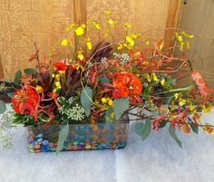 Fall colorful flower arrangement.  orange zinnia, burgundy leucadendron, yellow oncidium orchids, orange orchids, seeded eucalyptus, colorful beads.