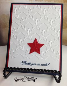 "By Patsy Collins. Navy card base. Red mat 5 1/4"" x 4."" Dry emboss  top three-fourths or so of white mat in ""Stars"" folder. Trim to 5 1/8"" x 3 7/8"" leaving enough of the unembossed area at the bottom for stamping a sentiment. Stamp sentiment in navy ink. Dry emboss red cardstock scrap in same folder, hand cut star, and adhere over one of the stars on the white mat."