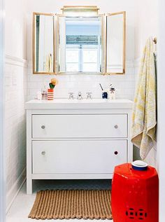 Inside a Fabulously Fresh Nashville Home  -- Gorgeous bright white kids bathroom with a pap of color from glassware and a bright glossy red ceramic garden stool. Love this colorful kids space! See the full home tour of the designers behind Pencil & Paper on our Style Guide!