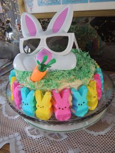 This was my Easter cake 2016..all it is..is two 9 inch round cakes frosted with what ever frosting you like and then Peeps bunnies placed around the edge and food coloring used on coconut..and a dollar store pair of sunglasses...