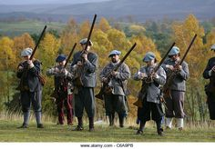 Members of [Fraser's Dragoons], a 17th century re-enactment society, loading their muskets - Stock Image