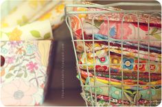 Wire baskets for fabric storage, organized but can still see the fabric options. One basket per color