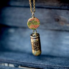 Natural unakite stone beads adorn this Unakite Stone Etched 45ACP Necklace. A scroll design has been etched into the casing.