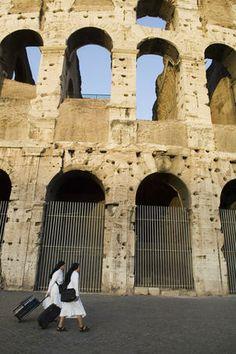Nuns walking past Colosseum, Roman Forum and Esquiline area.