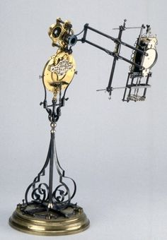 Microscope phakomètre; brass; part silvered; stand: moulded brass base; central steel column flanked by four thin steel scrolls, early 17th century, French school