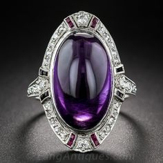 Art Deco Amethyst Cabochon Dinner Ring. This 1 inch long and lovely Jazz Age jewel, circa 1920s-30s, presents a deep royal purple, elongated cabochon oval amethyst. The enchanting gemstone is framed in platinum in consummate Art Deco style with small twinkling diamonds punctuated top and bottom by calibre rubies, and on the sides with black onyx. A decorative open work under gallery, platinum diamond-set shoulders and an engraved ring shank add the finishing touches...
