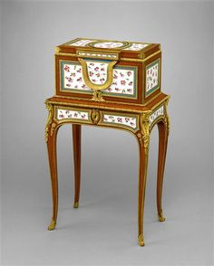 Martin Carlin ( born Germany lived in French,) 1730-1785)  Date     c. 1774      Oak carcass, veneered with tulipwood, holly, ebony, and amaranth, plaques of soft-paste porcelain, gilt-bronze mounts