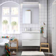Łazienka z białą szafką z umywalką, lustrem i ławkami z litego drewna sosnowego.