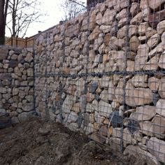 """Gabion wall installed. It was set with 2"""" steel pipe posts five feet deep through the center to anchor it to the ground. It was backfilled with concrete from the adjacent paving demolition."""