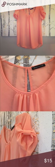 """Coral Size Small Adorable Top Coral colored size small top from Francesca's. Adorable bow detail on the sleeves. Cute cut out in the back. Small marking on the front of shirt. Semi to pretty sheet. Definitely need to wear something under it! From a smoke free home! Measurements (taken with garment laying flat): Front Length: 20"""", Back Length: 25-1/4"""", Sleeve Length: 5"""", Shoulder to Shoulder: 13-1/4"""", Pit to Pit: 17-1/2"""", Body Width: 19-1/2"""".  Material: 100% Polyester. Hand wash. Jella…"""