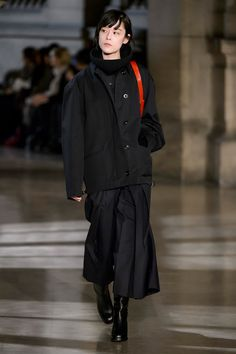 14. Short parka in water-repellent cotton bachette, trompe l'oeil sweater in stretch extrafine wool, knitted tube in pure new wool, pleated pants in water-repellent poly-wool twill, camera bag in vegetal tanned leather, boots in leather