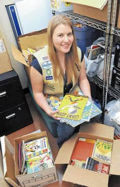 Annika Cushnyr sits among cases of books she has collected for her Girl Scout Gold Award project to create a library at the UNM Sandoval Regional Medical Center. Parents and children visiting the hospital will be able to pick out books and take them home. (JIM THOMPSON/JOURNAL)