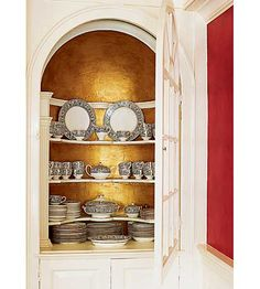 An original 1765 dining room china cupboard, painted with a gold interior, makes a dramatic backdrop for china display. | Photo: Laura Moss | thisoldhouse.com