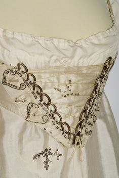 ephemeral-elegance:  Whitework Embroidered Spangled Evening Dress, ca. 1810 via Museum of Applied Arts, Budapest   What an odd front on this gown! Lace-up fronts on bodices are not something that you see all the time during this era, particularly not the way this is done, which gives the effect of a Georgian stomacher. The heavy-duty hardware used instead of eyelets is also quite interesting; it looks very weighty, and very chunky in comparison to the thin cord used to lace the bodice…