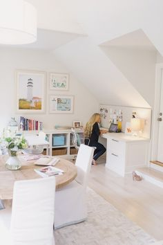 using all white helps office space recede into the rest of the space. love the Expedit-esque bookshelf on the long wall.