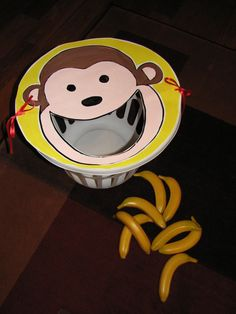"""Feed the Monkey"" Game - Make an animal face out of poster board and tie onto the top of a round laundry basket Use fake bananas to toss in."