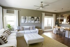 Love the white couches, neutral colors, love the big canvas family prints.