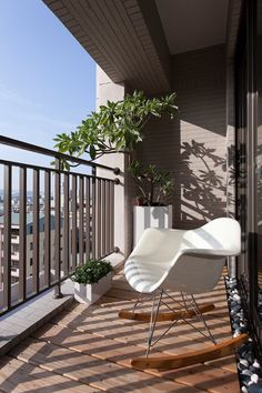 Interior Design, Brown Wall Tiles Metal Railing White Potted Plants Brown Yellowish Wooden Floor Rocking Armchair Balcony Furniture And Sliding Glass Door ~ Imposing Style of Home Decoration Bringing the Charm in the Appearance