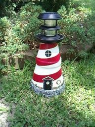 Flower pots stacked and painted to look like a lighthouse...solar light add at top for the light beacon!!!