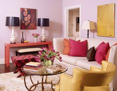 The energetic colors of this living room in Charleston set the tone for the whole house. Walls are painted Persian Pink by Porter. A Crate and Barrel sofa with a custom linen slipcover is paired with a vintage chair in yellow silk. Stool fabric is Herbert's Carnation Weave, David Hicks by Ashley Hicks for Lee Jofa.
