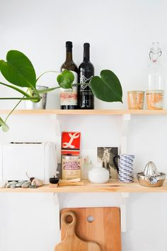 Wooden kitchen shelving displaying wine and various appliances.