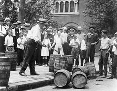 A crowd watches a man use an ax to destroy barrels of illicit beer. (Undated photograph)
