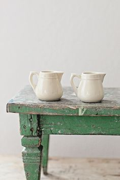 Vintage French Ironstone Creamers and green weathered wood farmhouse table
