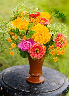 Do you love this marigold mix in a McCoy vase? Details + other ideas for summer centerpieces : http://www.midwestliving.com/homes/seasonal-decorating/colorful-summer-centerpieces/?page=2
