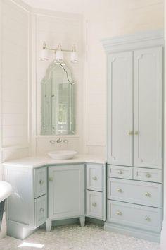 Blue bathroom features a blue corner washstand painted Benjamin Moore Woodlawn Blue topped with white marble and a bowl sink under an Allen   Roth Hovan Arch Frameless Mirror illuminated by a three light sconce alongside a mosaic marble floor.