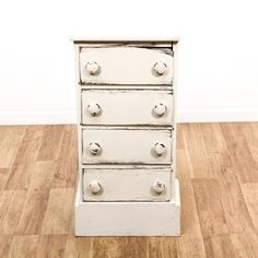 This cottage chic nightstand is featured in a solid wood with a distressed white paint finish. This narrow end table has 4 small drawers, simple carved details and round handles. Perfect little bed side table with storage! #cottagechic #dressers #nightstand #sandiegovintage #vintagefurniture