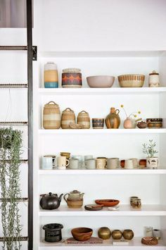curated ceramics collection on open white shelving. / sfgirlbybay