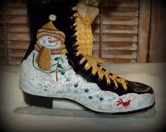 Here we are offering this Handpainted Snowmen Ice Skate. The Right side of the skate features a melting snowman in a yellow and gold plaid scarf and hat with a little red bird sitting on the snow. The snowman is painted in what is called a crackle effect. The left side of the skate features a melting snowman in a blue plaid coat and sweater holding a candle in the air with a couple cardinals in the snow. The scarf around his neck matches the material used in the skate lacing. Jenny has added…