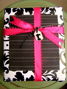 Plain white shirt boxes decorated with scrapbook papers and ribbon.  Blog has more ideas.