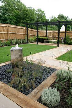 A stainless steel water feature adds a contemporary twist. #garden Garden Fencing trellis garden ideas