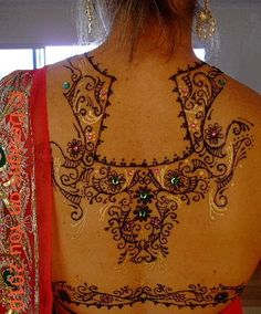 Lovely! Her back is hennaed and bejeweled.