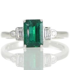 An 18ct white gold cluster ring featuring a 1.20ct emerald cut emerald accompanied by a GRS certificate set in four claws above a railed gallery set between a pair of baguette cut diamonds each bezel set along the length of the emerald with a single round brilliant cut diamond of colour F-G clarity VS bezel set at either side marking the beginning of the plain polished tapering band. #Rutherford #Melbourne