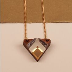 Metallic Grey Chevron Necklace ($31) ❤ liked on Polyvore featuring jewelry, necklaces, triangle necklaces, wooden jewelry, triangle pendant, cable chain necklace and wooden pendant necklace