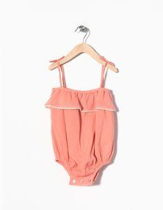 Macacão de alças 100% algodão com folho e três botões madrepérola entrepernas para vestir facilmente.