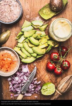 Geschnittene Avocado mit Messer und Kochzutat, avocado and healthy fresh ingredients, healthy food, wood board