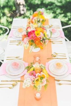Apricot table runner on white linens with white and gold place settings, accented with pink and yellow flowers. What a happy looking table!