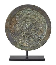 CHINESE SILVERED BRONZE MIRROR  POSSIBLY TANG DYNASTY  with raised bosses and scroll work decoration, with later stand   18cm diam