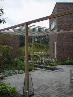 Moderne stadstuin. Pergola hardhout met gegalvaniseerde cv buis. Betontegel groot zonder facet. Weelderige beplanting. Spiegelvijver.