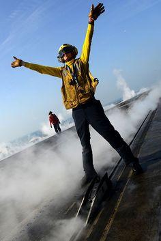 Aviation Boatswain's Mate (Handling) 3rd Class Andrew Cox, directs an aircraft to a catapult shuttle on the flight deck of the aircraft carrier USS JOHN C. STENNIS (CVN 74). USN photo.